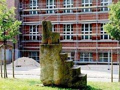Rekonstruovaná budova Gymnázia J. K Tyla v Hradci Králové, před ní židle na vysokém podstavci od finského sochaře Bjarna Lönnroose.