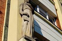Socha úředníka na budově v hradecké Divišově ulici.
