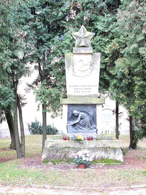 Památník padlým rudoarmějcům stradičními symboly hvězdy, srpu a kladiva položeném na svázaných snítkách vavřínu a lípy.