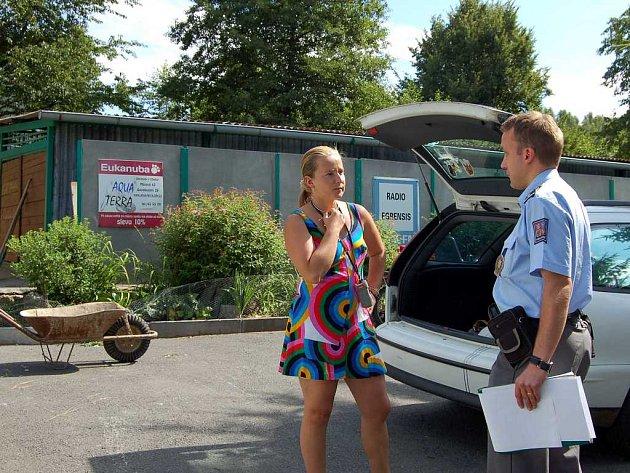 Marie Lokingová s jedním z vyšetřujících policistů. Kolečko v pozadí zloděj využil k odvezení krmiva pro psy