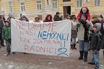 """PŘED MARIÁNSKOLÁZEŇSKOU RADNICÍ se také objevilo několik transparentů. Andrea Gruntorádová (na snímku vpravo) donesla jeden hlásající: """"Nedáme naši nemocnici, tak jdeme na radnici!"""""""