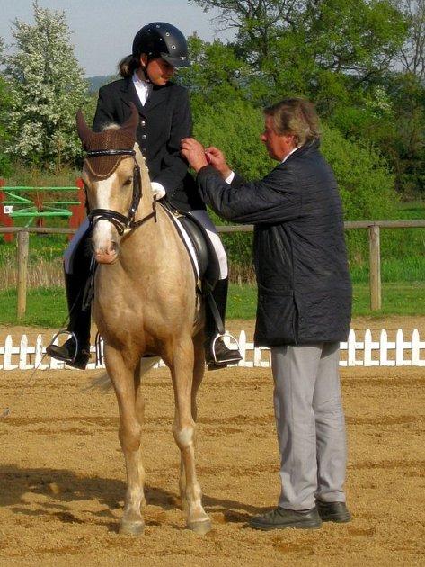 KAROLÍNU ŠIMÁČKOVOU na koni Dancer, vítězku první soutěže, dekoruje německý rozhodčí Harald Witt.