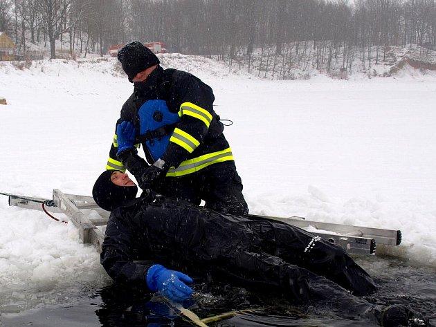 CVIČENÍ ZÁCHRANY ČLOVĚKA, který se propadl do ledové vody, zkoušejí hasiči a policejní potápěči na Jesenici u Chebu již podruhé. Podobně trénují i v létě.