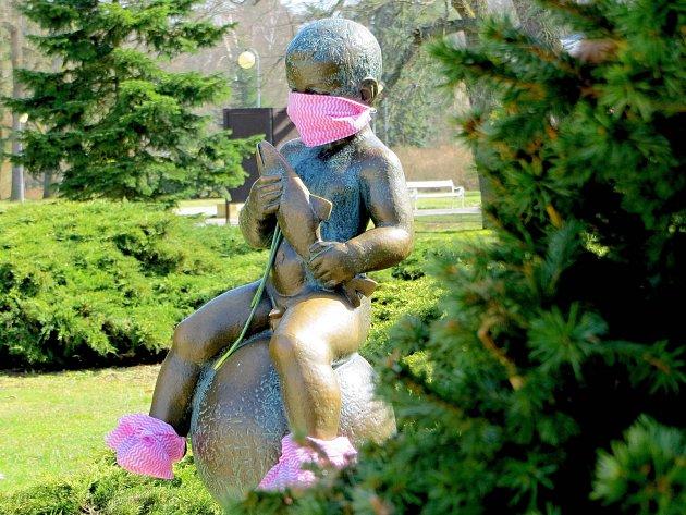 Lidé navlékli zdravotní roušku isoše malého Františka, který zdobí jeden zparků ve Františkových Lázních. Lidé se usochy rádi fotí a ihned svoje fotografie sdílejí na sociálních sítích. Mimo jiné má František navlečené ibezpečnostní bačkůrky.