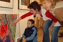Hana Olišarová, která měla v sobotu na starosti výtvarnou dílnu v chebské galerii G4, ukazuje na hotovém šátku, jak se s barvami na hedvábí pracuje.