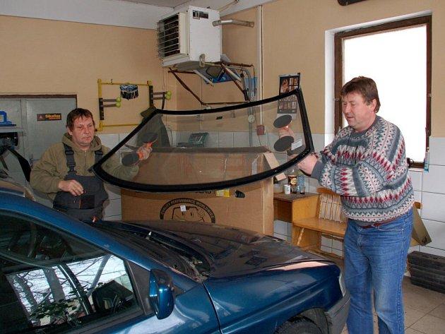Vojtěch Kufner (vpravo) při výměně čelního skla automobilu