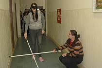 PŘI BESEDĚ na téma chování ke zrakově postiženým si Zuzana Ronnerová vyzkoušela chůzi s klapkami na očích a slepeckou holí.