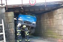 Nepříjemné překvapení čekalo včera na řidiče nákladního vozidla při projíždění pod železničním viaduktem v Nebanicích na Chebsku. Šofér si totiž neuvědomil, že na korbě veze bagr, který je příliš vysoký na to, aby pod viaduktem projel.