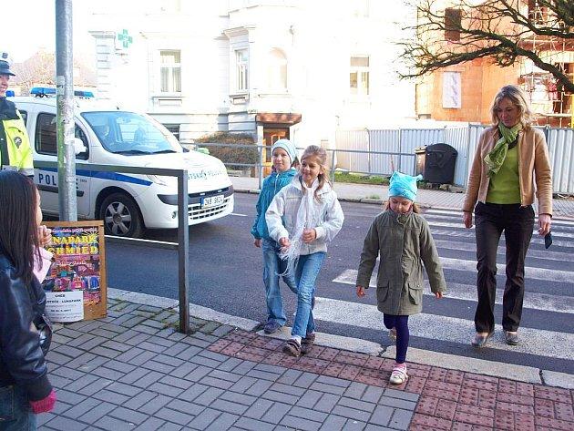 SPRÁVNĚ! Školačky Terezka Hrušková (zleva), Klárka Síglová a Terezka Procházková z 2. C chebské 2. Základní školy si za asistence své třídní učitelky Ivany Hruboňové vyzkoušely, jak bezpečně přejít vozovku.