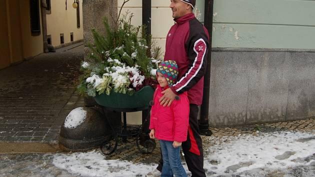 """ADÉLKA AGNES obdivuje s tatínkem chebskou vánoční výzdobu. """"Opravdu pěkné jsou i tyto ozdobné květináče,"""" řekla."""