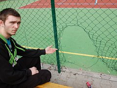 Poničený plot na sportovním hřišti