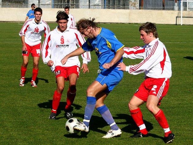 Doubravecký záložník Pavel Vaigl (uprostřed v modrém dresu) se snaží probít obranou Holýšova v utkání jedenáctého kola fotbalového přeboru Plzeňského kraje.