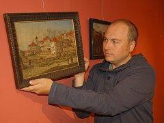 """VÝSTAVA OBRAZY CHEBU začne v muzeu a Galerii výtvarného umění ve čtvrtek. K vidění bude například obraz, který v pondělí instaloval Zbyněk Černý. """"Jde o zákoutí starého Chebu u Schäckovy věže od malíře Franze Schilhabla,"""" uvedl."""