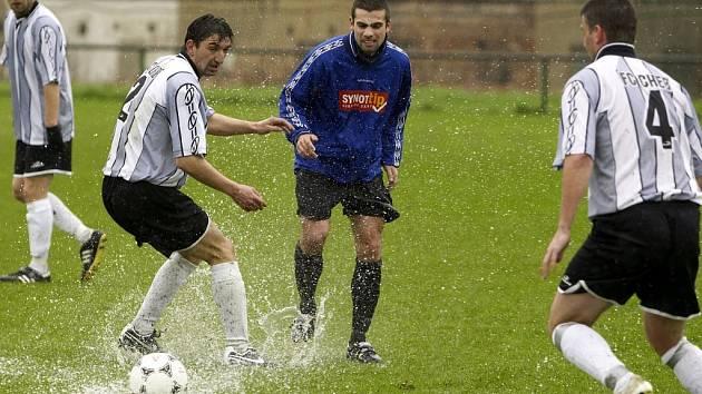 O PODMÁČENÉM TERÉNU  při zápase FC Cheb – Ostrov vypovídá snímek, na kterém  chebský Benkovský (vlevo) se snaží zpracovat míč v kaluži.