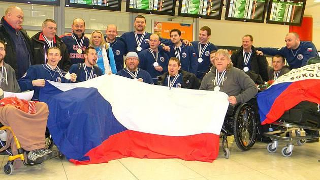 SLEDGEHOKEJOVÍ REPREZENTANTI s medailemi zapózovali také po příletu na ruzyňské letiště.