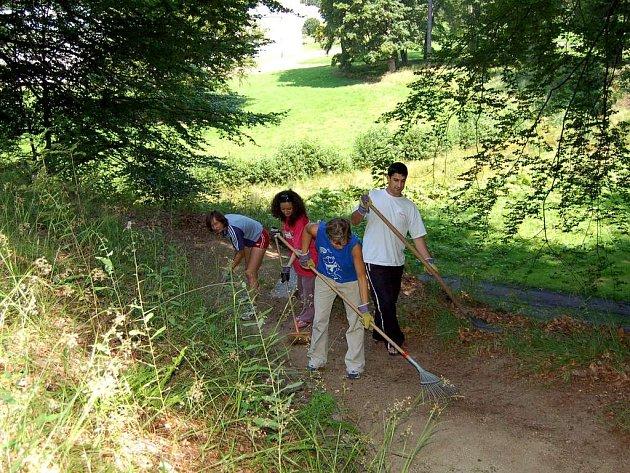 Zahraniční studenti při práci na úklidu parku u zámku v Kynžvartě