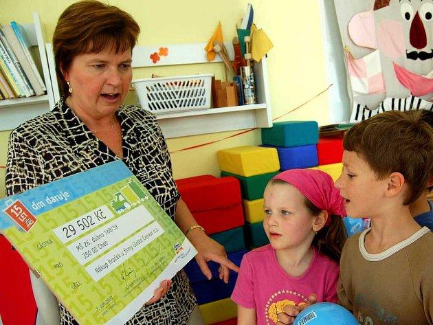 DAR POTĚŠIL.  Děti zářily nadšením, když spolu s ředitelkou školky Ludmilou Mračkovou přebíraly šek , díky kterému dostanou nové hračky. Některé si už cifru  dokázaly samy přečíst.