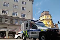 U šedé budovy za policejním autem došlo k napadení ženy