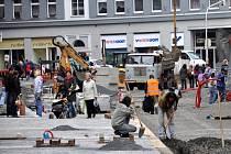 Rekonstrukce I. části pěší zóny v Chebu. Dlaždiči už položili část nové dlažby od křižovatky s Evropskou ulicí. Na portější straně likvidují stavební dělníci zasypané základy bývalých veřejných záchodků.