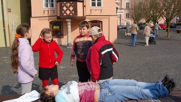 HLÍDKA MLADÝCH ZDRAVOTNÍKŮ. Nejmladší účastníci, žáci třetí třídy z chebské základní školy v Hradební ulici ošetřili ženu s bolestí břicha. Nikola Arpášová (druhá zleva) právě předvádí, jak zavolat rychlou záchrannou službu.
