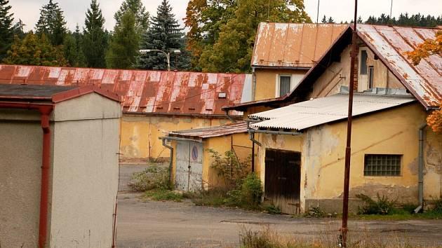 Současná podoba lokality. Keře, tráva a staré budovy