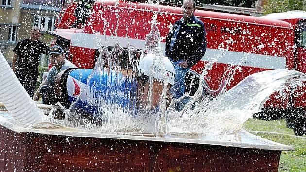 Ponořit koš do kádě s vodou tak, aby zůstali hasiči suší, je nemožné. Na snímku je soutěžící ze skalenského dívčího družstva