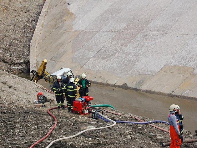 POTOPENÝ BAGR na chebské přehradě Skalka zaměstnal na několik hodin jednotky hasičů, které pomocí čerpadel stroj vysvobodily.