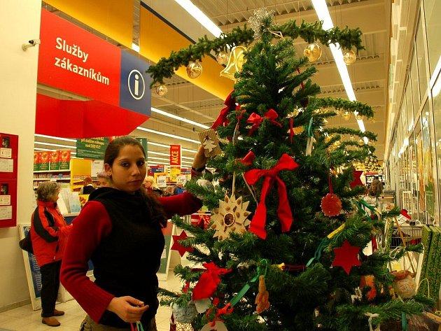 VÁNOČNÍ STROMEČEK v chebském Tescu právě ověšuje vánočními přáníčky Katka Typanová z ašsckého dětského domova.