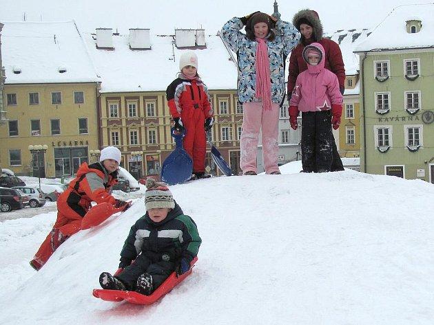 Zařádit si na kopeček utvořeného ze shrnutého sněhu na chebské náměstí přišlo několik dětí.