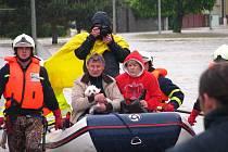 Před valící se řekou prchali manželé Němčákovi z Troubek nad Bečvou už podruhé. Nejprve to bylo v červenci před 13 lety, kdy jim voda vzala dům. V úterý dopoledne museli usednout do člunu záchranářů znovu.