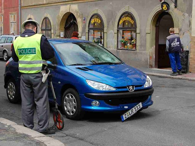 Policista vyšetřuje dopravní nehodu, při které došlo ke zranění mladé ženy