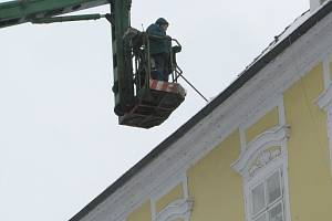 Sníh ze střech historických domů na chebském náměstí Krále Jiřího z Poděbrad museli pracovníci technických služeb odstraňovat pomocí vysokozdvižné plošiny