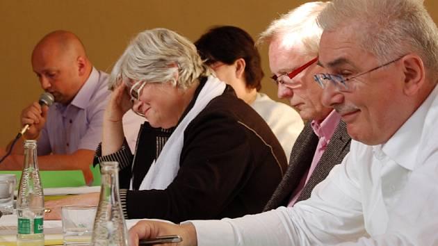 O SOUČASNÉM NÁZORU na vzájemnou spolupráci hovoří výrazy ve tvářích Františka Šnajdaufa (první zprava) a Lenky Malkovské právě při vyjádření Romana Knedlíka  (v pozadí s mikrofonem) při jednání  františkolázeňského zastupitelstva.