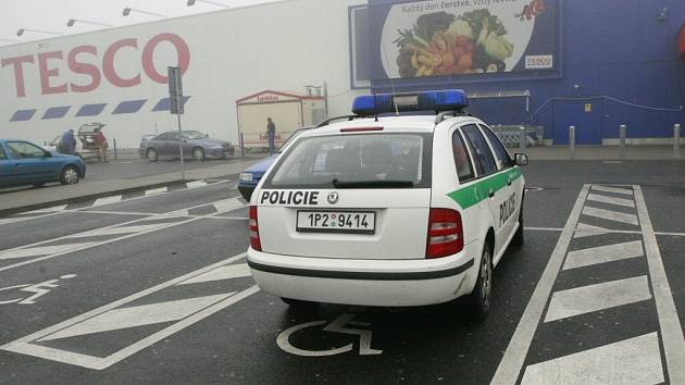 Policejní vozidlo odstavené na místě označeném vodorovnou dopravní značkou jako parkoviště pro invalidy. Jen chybějící svislá dopravní značka uchránila policisty od přísného trestu