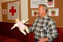 ŘEDITEL ČESKÉHO ČERVENÉHO KŘÍŽE pro oblast Sokolovska a Chebska Stanislav Fletter ukazuje dětem na figuríně dítěte, jak správně poskytnout první pomoc.