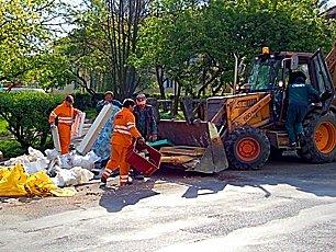 Pracovníci technických služeb uklízejí nepořádek kolem kontejnerů