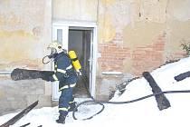 Uskladněné dříví hořelo v jednom z mariánskolázeňských domů. Hasiči museli požár uhasit v maskách.