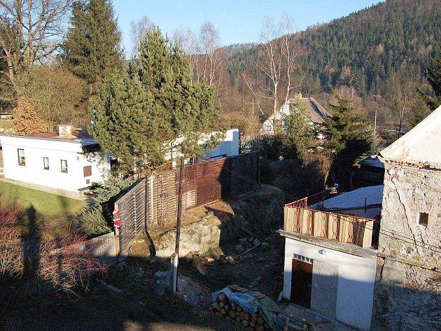 Ani třímetrová palisáda mezi domem Klimešových (vlevo) a Schneiderových neřeší sousedské problémy v Krásném Jezu.