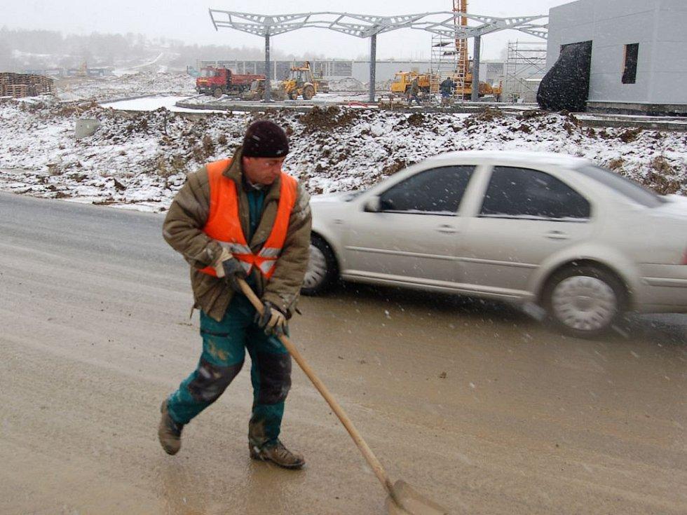 Zbavit silnice nánosů bahna není jednoduché. Vedle cisteren s vodou, které povrch oplachují, tak přichází na řadu lidská síla a lopata.