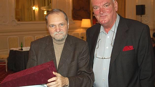 Ředitel festivalu Tourfilm Josef Schütz (vlevo) a předseda mezinárodní poroty Jiří Mikeš nad cenou, kterou věnoval hejtman kraje. Tu získal snímek Pavla Riese Karlovarské obrazy.