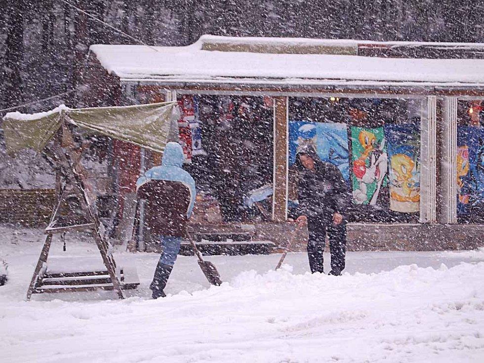 Vietnamští obchodníci ve stánku u Abertamské křižovatky mají se sněhem plné ruce práce. Na lyžování to ale zatím není.