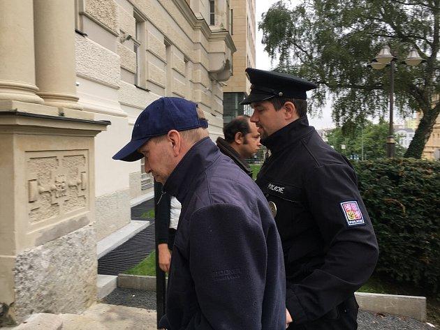 Policie přivádí obviněného muže do soudní budovy.