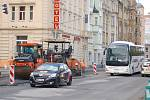 """Na křižovatce """"u Becherovky"""" v centru Karlových Varů pokládají silničáři nový asfaltový povrch."""