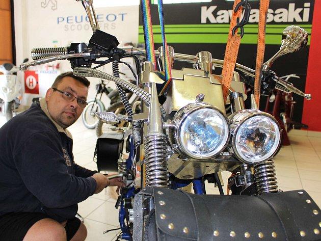 Josef Roštejnský se věnuje v dílně opravě motocyklu. V tomto případě šlo o náročnější údržbu.
