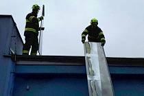 Ze zásahu hasičů. Z události v Sokolově, kde vítr uvolnil část oplechování střechy na mateřské škole.