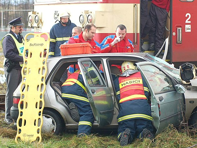 Záchranáři ošetřují řidiče, který nezastavil před přejezdem v Nové Roli a srazil se tak s motorovým vlakem.