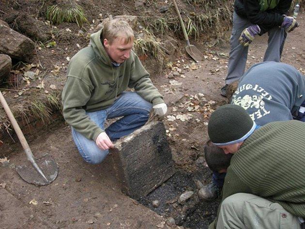 Záchrana náhrobních kamenů. Brigádník Lukáš Toman vyzdvihuje jeden ze zatím čtyř desítek objevených náhrobních kamenů z bývalého židovského hřbitova v Bečově nad Teplou.