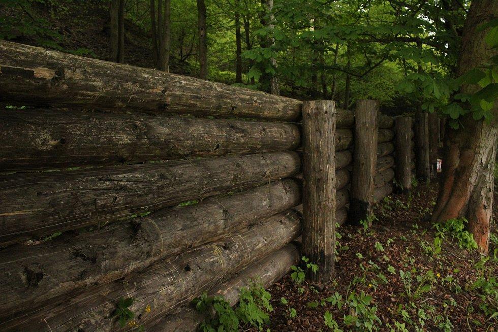 Skalní masiv na úpatí vojenského prostoru zajišťuje masivní plot z kulatiny.