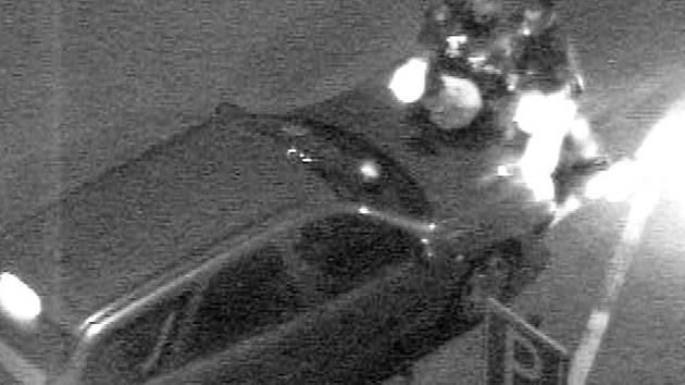 Z AUTA DOLŮ! Snímek z městského monitorovacího kamerového systému zachycuje karlovarské strážníky v okamžiku, kdy sundavali opilého muže z kapoty auta.