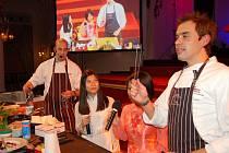 """Kluci v akci v akci. Že i vaření může být skvělá zábava, dokazují z obrazovek pánové Ondřej Slanina (vlevo) a Filip Sajler (vpravo). Při včerejším živém vystoupení ve Slavnostním sále Grandhotelu Pupp jim byly """"k ruce"""" i dvě půvabné Vietnamky."""